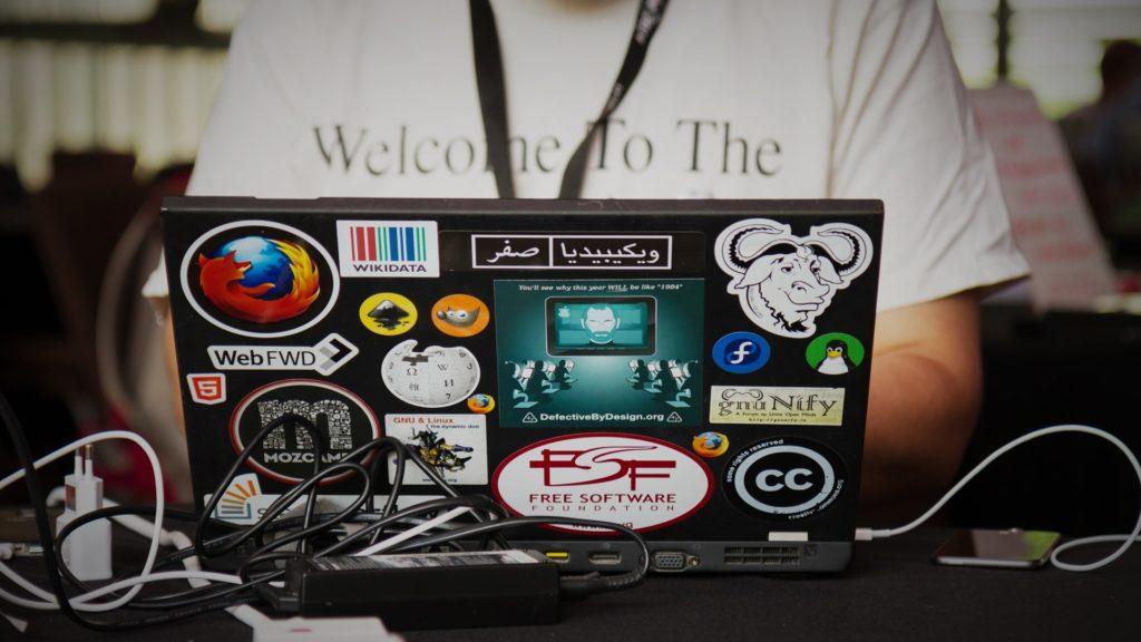 accumulation de sticker de projets open source sur un ordinateur portable d'un informaticien geek et libriste à fond